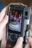 Женщина делает фотографию торта используя mirrorless камеру стоковое изображение rf