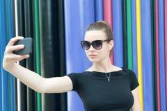 Женщина делает selfie с smartphone в Париже, Франции Женщина с мобильным телефоном на красочной предпосылке Девушка в солнечных о стоковое изображение