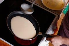 Женщина делая блинчики в кухне Стоковое Изображение RF