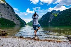 Женщина делая гимнастику на берегах Königssee стоковое фото rf