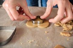 Женщина делая домодельные печенья имбиря в форме сердец на a Стоковое Изображение RF