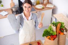Женщина делая здоровую еду стоя усмехающся в кухне Стоковое Фото