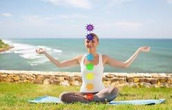 Женщина делая йогу в представлении лотоса с 7 chakras стоковое фото