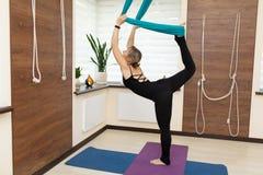 Женщина делая йогу мухы протягивая стоять на одной ноге на том основании и во-вторых в гамаке Образ жизни пригонки и здоровья стоковое изображение rf