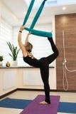 Женщина делая йогу мухы протягивая стоять на одной ноге на том основании и во-вторых в гамаке Образ жизни пригонки и здоровья стоковое фото rf