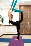 Женщина делая йогу мухы протягивая стоять на одной ноге на том основании и во-вторых в гамаке r стоковая фотография rf