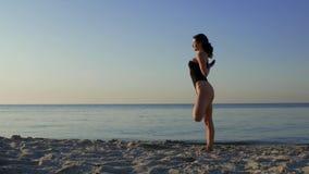 Женщина делая йогу на пляже против фона моря или океана фитнес йоги и здоровый образ жизни солнце, море, лето 4K видеоматериал