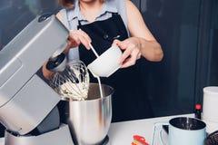 Женщина делая машину торта хлебопекарни смесителя стоковые фотографии rf