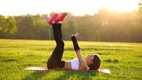 Женщина делая подбрюшные хрусты работает на циновке фитнеса в парке лета в замедленном движении на заходе солнца видеоматериал
