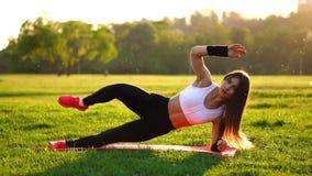 Женщина делая подбрюшные хрусты работает на циновке фитнеса в парке лета в замедленном движении на заходе солнца сток-видео