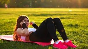 Женщина делая подбрюшные хрусты работает на циновке фитнеса в парке лета в замедленном движении на заходе солнца акции видеоматериалы
