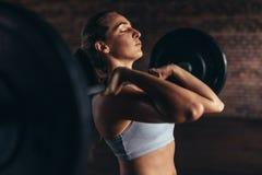 Женщина делая поднятие тяжестей в спортзале стоковое изображение rf