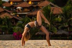 Женщина делая представление моста йоги на пляж Стоковые Фото