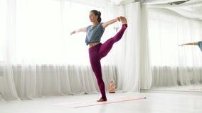 Женщина делая представление рук-к-больш-пальца ноги йоги на студии акции видеоматериалы
