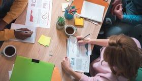 Женщина делая примечания на бумаге на таблице Стоковые Изображения