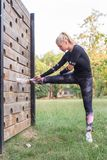 Женщина делая протягивающ тренировку деревянной стеной outdoors стоковая фотография rf