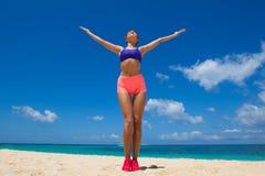 Женщина делая разминку на пляже стоковые фото