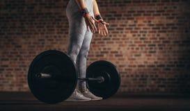 Женщина делая разминку поднятия тяжестей на спортзале стоковые фото