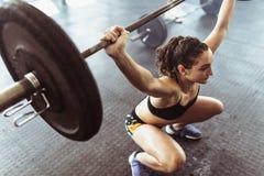 Женщина делая deadlift с тяжелыми штангами в спортзале Стоковая Фотография RF