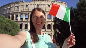 Женщина делая selfie около Colosseum в Риме, Италии Девочка-подросток развевая итальянский флаг в замедленном движении акции видеоматериалы