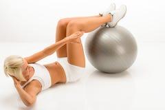 Женщина делая sit-ups на белизне шарика пригодности Стоковые Фотографии RF