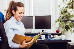 Женщина дела усмехаясь держа бумаги стоковая фотография