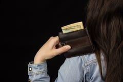Женщина держа бумажник с деньгами, концом-вверх, черной предпосылкой, банкнотой, долларами стоковое фото