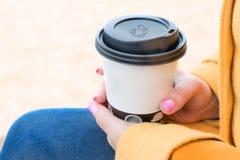 Женщина держа бумажную кофейную чашку в ее руке, женщин с чашкой coffe Стоковые Изображения RF