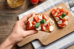 Женщина держа вкусное bruschetta с томатами вишни Стоковые Фото