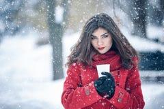 Женщина держа горячее питье снаружи Стоковые Изображения