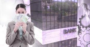 Женщина держа деньги и высокие здания кренят с предпосылкой шестерней cog Стоковое фото RF