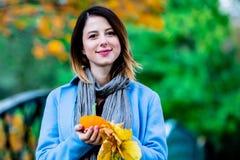 Женщина держа желтое дерево клена выходит и тыква в парк autum стоковое изображение rf
