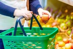 Женщина держа зеленую корзину для товаров и кладя яблоко в корзину Овощи и плодоовощи на заднем плане женщина ног принципиальной  Стоковое Изображение RF