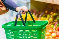 Женщина держа зеленый пустой конец корзины для товаров вверх с овощами и плодоовощами на заднем плане женщина ног принципиальной  Стоковая Фотография RF