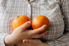 Женщина держа 2 зрелых апельсина в ее руках Стоковая Фотография RF