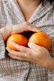 Женщина держа 2 зрелых апельсина в ее руках Стоковые Изображения RF