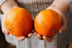 Женщина держа 2 зрелых апельсина в ее руках Стоковое Изображение