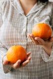 Женщина держа 2 зрелых апельсина в ее руках Стоковые Фото