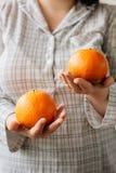 Женщина держа 2 зрелых апельсина в ее руках стоковое фото