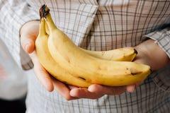 Женщина держа 3 зрелых банана в оружиях Стоковое Фото