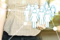 Женщина держа иллюстрацию значков людей подключила к каждому надгоризонтному Стоковые Изображения