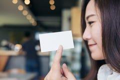 Женщина держа и показывая пустую визитную карточку с стороной smiley Стоковые Изображения