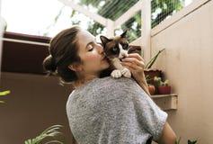 Женщина держа и целуя ее кота стоковая фотография