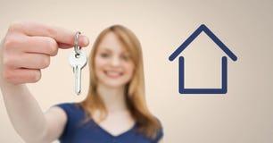 Женщина держа ключевой с значком дома перед виньеткой Стоковые Изображения