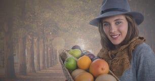 Женщина держа корзину плодоовощ в осени в лесе Стоковая Фотография