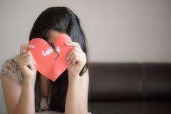 Женщина держа красное разбитый сердце с текстом влюбленности Стоковые Фото