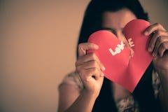 Женщина держа красное разбитый сердце с текстом влюбленности Стоковые Изображения
