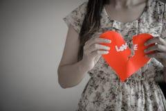Женщина держа красное разбитый сердце с текстом влюбленности Стоковая Фотография
