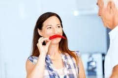 Женщина держа красный пеец рядом с ее стороной Стоковое Изображение RF