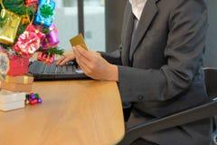женщина держа кредитную карточку используя компьютер для онлайн покупок Бушель стоковая фотография rf